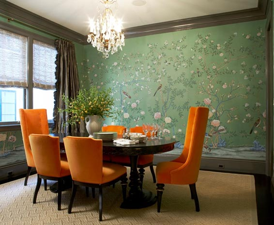 massucco-warner-miller-dining-room-oval-table-crystal-chandelier-bird-green-wallpaper-orange-upholtered-dining-chairs